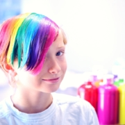 child with multi colored dyed hair with hair dye bottles sitting behind them.